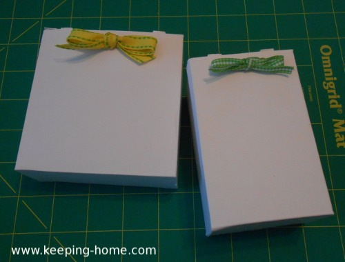 Adhesive bandage boxes turned wrong-side out and decorated with yellow and green ribbon.